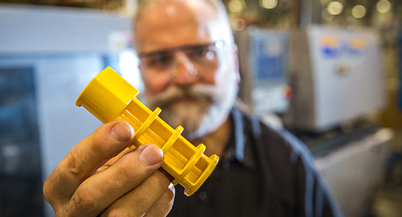technician holding yellow injection molded part from protolabs